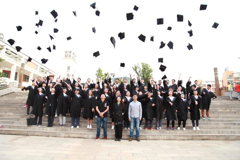 学生たちが帽子を放り投げる様子