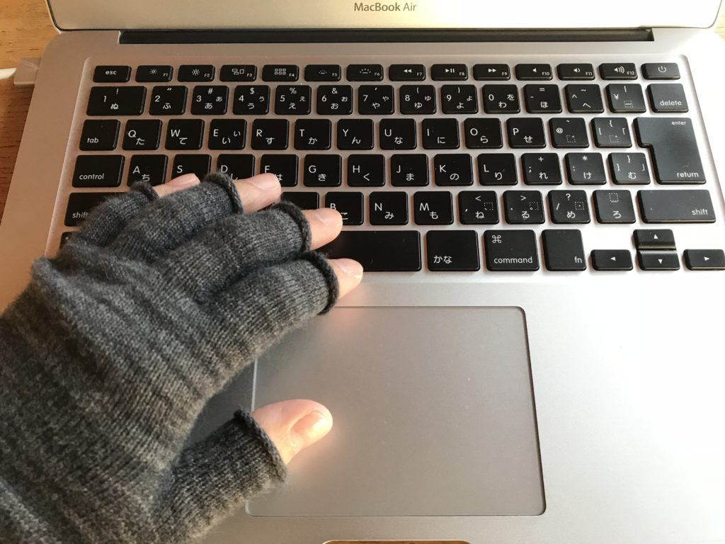 手袋をはめてパソコンを打つ手