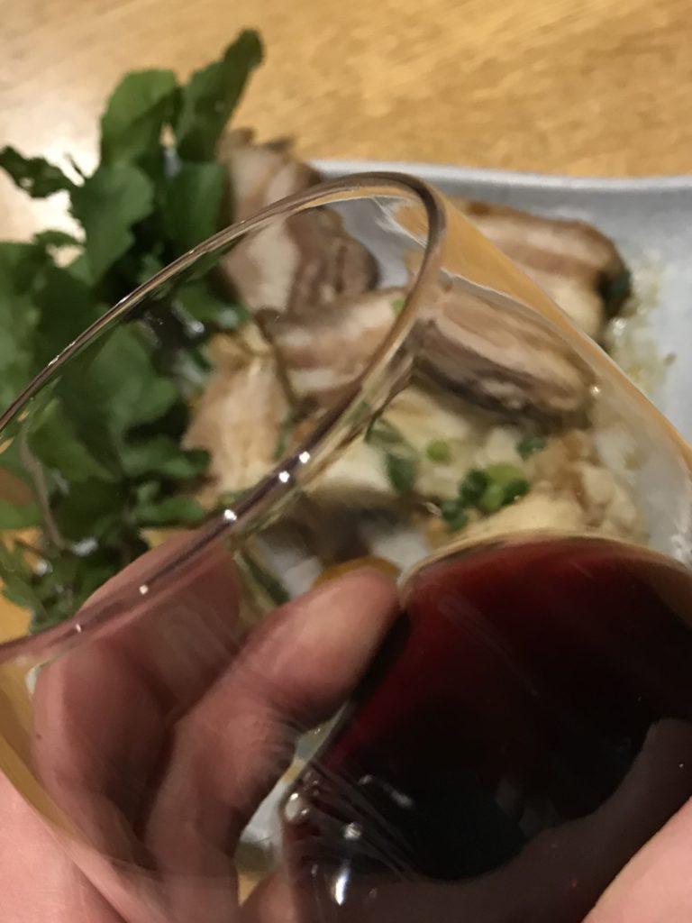 ワインを注いだワイングラスを持った手