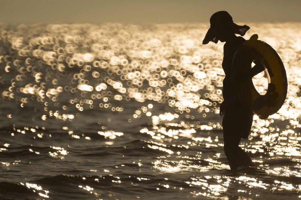 夕日をバックに海岸を歩く女性
