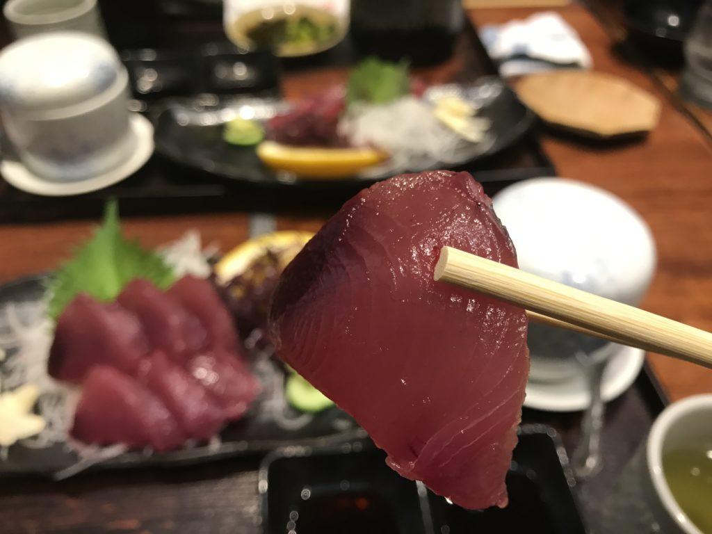 いけす料理『なにわ』の【びやびやかつお】の刺身を一切れ箸で摘み上げた様子