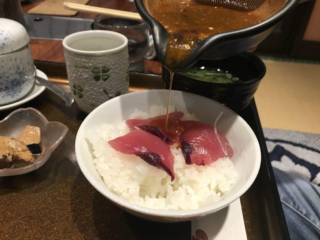 いけす料理『なにわ』の【びやびやかつお】飯定食のかつおを飯に乗っけて特製タレをかける様子