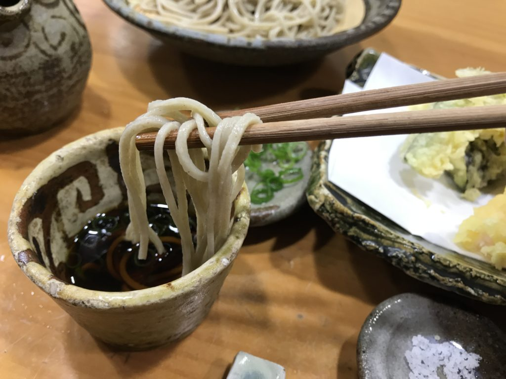 『蕎麦まえの』の【天ぷらせいろ】のそばを箸でつまみ上げた様子