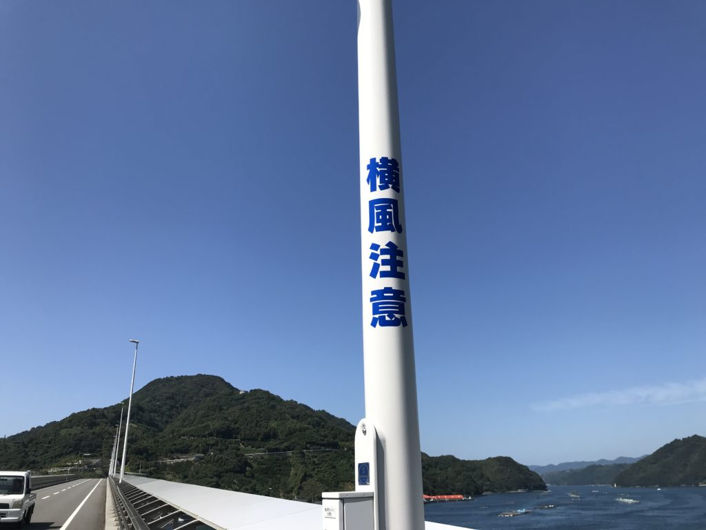『九島大橋』の街灯に書かれた「横風注意」の文字