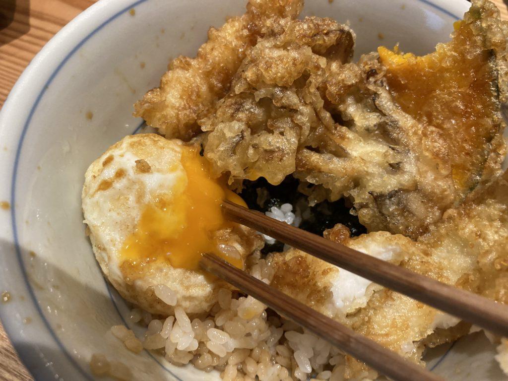 『天婦羅天よし』の天丼の半熟卵を箸でつまんだ様子
