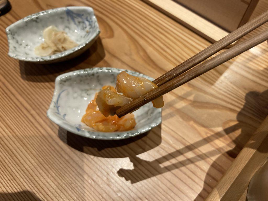 『天婦羅天よし』の貝柱の明太和えを箸でつまみ上げた様子